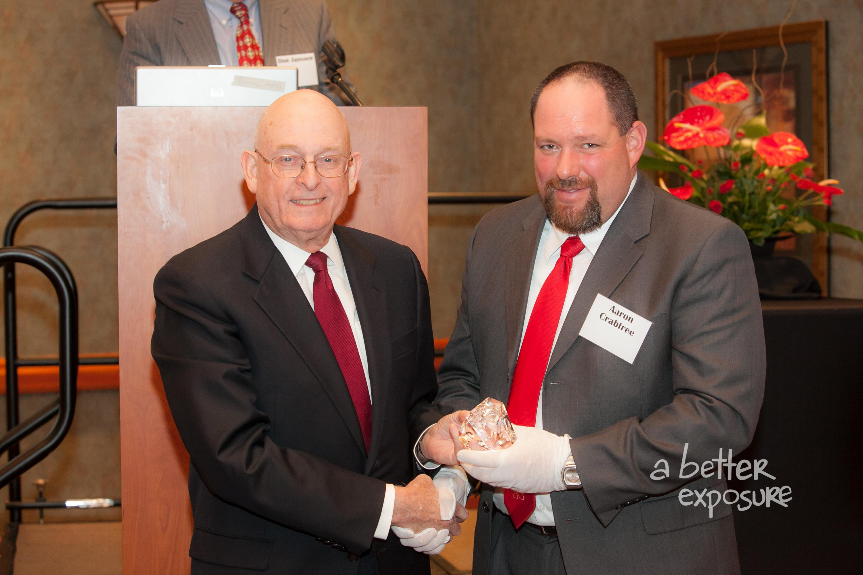 President Aaron Crabree presents Larry Gibbs with a gift from the Great Plains Federal Tax Institute